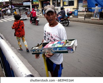 ANTIPOLO CITY, PHILIPPINES - JULY 19, 2017: A man sells cigarettes, candies and snack items along a street in Antipolo City.