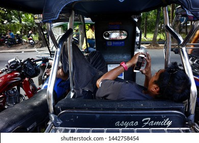ANTIPOLO CITY, PHILIPPINES – JULY 3, 2019: A Filipino man lies down in a tricycle cab and plays a video game on a smartphone.