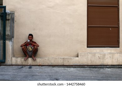 ANTIPOLO CITY, PHILIPPINES – JULY 3, 2019: An adult Filipino man rests outside of a building and plays a game on his smartphone.