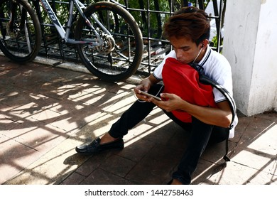 ANTIPOLO CITY, PHILIPPINES – JULY 3, 2019: A Filipino man sits on the pavement while playing a video game on a smartphone at a public park.