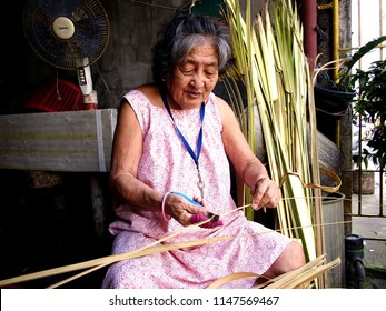 ANTIPOLO CITY, PHILIPPINES - JULY 30, 2018: An old lady trims dried palm leaves to be used as wrapper for steamed glutenous rice locally known as Suman.