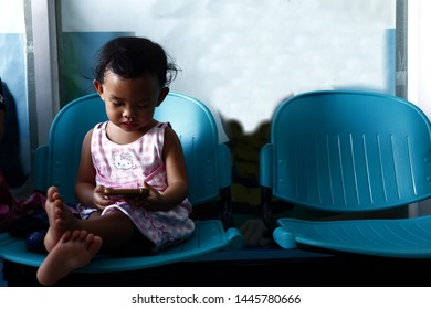 ANTIPOLO CITY, PHILIPPINES – JULY 5, 2019: Young Asian girl plays a video game on a smartphone while at a waiting area.
