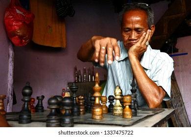 ANTIPOLO CITY, PHILIPPINES - MARCH 11, 2019: Filipino men relax and play a game of chess inside their restaurant.