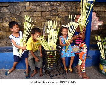 ANTIPOLO CITY, PHILIPPINES - MARCH 19, 2016: Vendors prepare palm leaves to be sold to church patrons in preparation for the Palm Sunday celebration outside a church in Antipolo City, Philippines