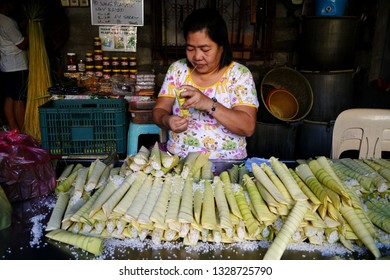 ANTIPOLO CITY, PHILIPPINES - MARCH 2, 2019: A food vendor wraps raw glutenous rice into palm leaves as she prepares to steam it and cook it into a Filipino delicacy called Suman.