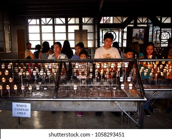 ANTIPOLO CITY, PHILIPPINES - MARCH 29, 2018: Catholic devotees pray and light prayer candles in Antipolo Cathedral or Our Lady of Peace and Safe Voyage.