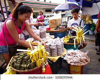 ANTIPOLO CITY, PHILIPPINES - MARCH 29, 2018: Street vendors sell Suman or steamed glutenous or sticky rice and other local delicacies outside the Antipolo Cathedral.