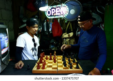 ANTIPOLO CITY, PHILIPPINES - MARCH 9, 2019: Filipino men relax and play a game of chess inside their repair shop after a day's work.