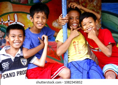 ANTIPOLO CITY, PHILIPPINES - MAY 1, 2018: Young Asian boys smile and pose for the camera while sitting on a steel fence.