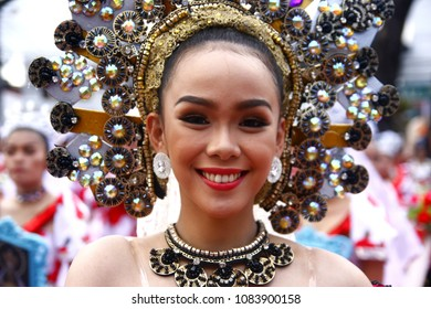 ANTIPOLO CITY, PHILIPPINES - MAY 1, 2018: Parade participants in their colorful costumes march and dance in the street during the Sumakah Festival in Antipolo City.