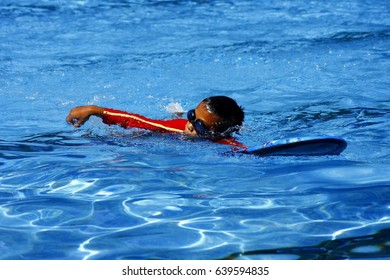 ANTIPOLO CITY, PHILIPPINES - MAY 10, 2017: A kid learns how to swim in a pool with the help of a kickboard.