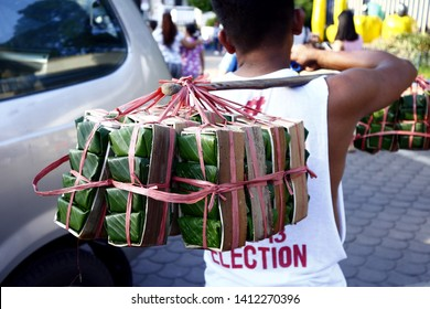 ANTIPOLO CITY, PHILIPPINES – MAY 30, 2019: A street vendor peddles Kesong Puti or cheese made from carabao milk wrapped in banana leaves at a public park.