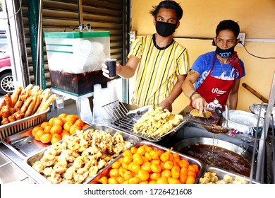 Antipolo City, Philippines - May 7, 2020: Street food vendors sell assorted deep fried food in their food cart along a sidewalk.