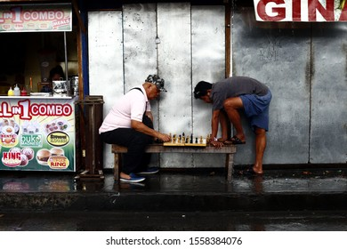 ANTIPOLO CITY, PHILIPPINES – NOVEMBER 12, 2019: Two adult Filipino men play a game of chess by a sidewalk.