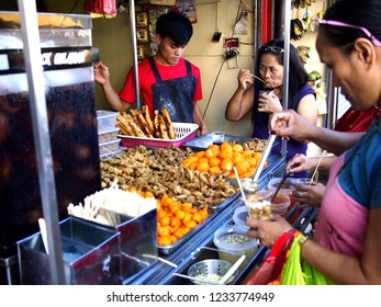 ANTIPOLO CITY, PHILIPPINES - NOVEMBER 13, 2018: Customers of a snack food kiosk pick their choice of fried food.