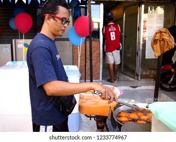 ANTIPOLO CITY, PHILIPPINES - NOVEMBER 13, 2018: A man deep fries duck eggs in a flour batter called Kwek kwek in his food kiosk