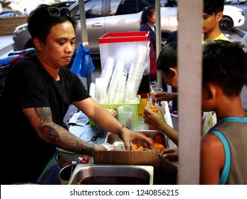 ANTIPOLO CITY, PHILIPPINES - NOVEMBER 19, 2018: A street vendor sells deep fried duck, quail and chicken eggs on his food cart at a sidewalk.
