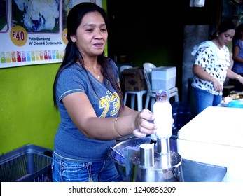 ANTIPOLO CITY, PHILIPPINES - NOVEMBER 24, 2018: A food vendor cooks Puto Bumbong or ground glutenous rice steamed in bamboo at her store.