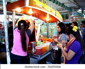 ANTIPOLO CITY, PHILIPPINES - NOVEMBER 25, 2017: Customers line up and buy snack food from a food cart at a public park.