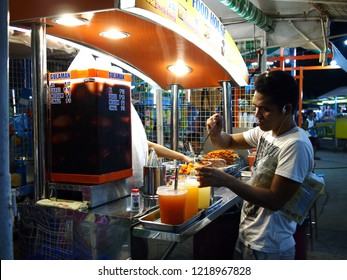 """ANTIPOLO CITY, PHILIPPINES - OCTOBER 27, 2018: A customer puts sauce on deep fried quail eggs locally known as """"Kwek kwek"""" from a food stall."""