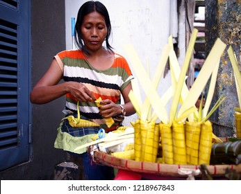 ANTIPOLO CITY, PHILIPPINES - OCTOBER 27, 2018: A street vendor sells Suman or steamed glutenous rice wrapped in palm tree leaves at her makeshift store on a sidewalk.