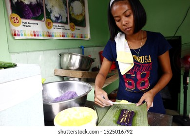 ANTIPOLO CITY, PHILIPPINES – OCTOBER 3, 2019: Food vendor cooks local delicacy called puto bumbong or ground purple glutenous rice cooked in bamboo tubes normally sold during the Christmas season.