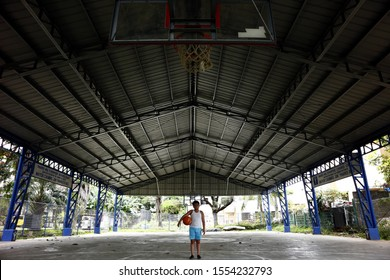 ANTIPOLO CITY, PHILIPPINES – OCTOBER 30, 2019: Young Filipino boy stands on the free throw line of a basketball court and holds a basketball.