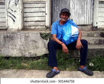 ANTIPOLO CITY, PHILIPPINES - OCTOBER 6, 2016: An old Asian man sitting on a sidewalk