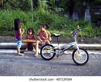ANTIPOLO CITY, PHILIPPINES - SEPTEMBER 21, 2016: Young girls play and talk while sitting at a sidewalk.