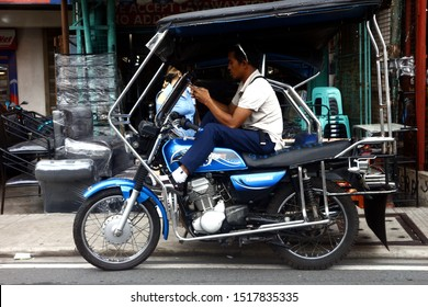 ANTIPOLO CITY, PHILIPPINES – SEPTEMBER 23, 2019: Tricycle driver rests and uses smartphone while waiting for passenger.