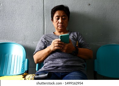 ANTIPOLO CITY, PHILIPPINES - SEPTEMBER 6, 2019: Adult Filipino woman uses her smartphone while sitting on a chair at a waiting area.