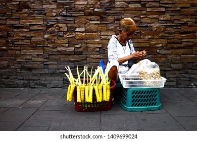ANTIPOLO, RIZAL, PHILIPPINES - MAY 18, 2019: A street vendor sells a Filipino delicacy called Suman or steamed glutenous rice wrapped palm leaves and toasted cashew nuts.