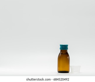 Antipyretic syrup in amber bottle with blank label and a plastic measuring cup on white background with copy space