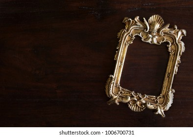 antiq golden photo frame in Rococo style, on dark rustic wooden background