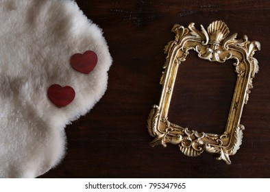 antiq golden photo frame in Rococo style, on dark rustic wooden background with white Tuscan sheepskin and hearts