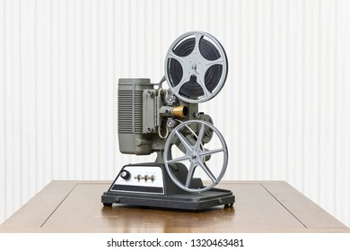 Antique 8mm home movie projector on wood table.
