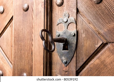 antique aged key in strong wooden door