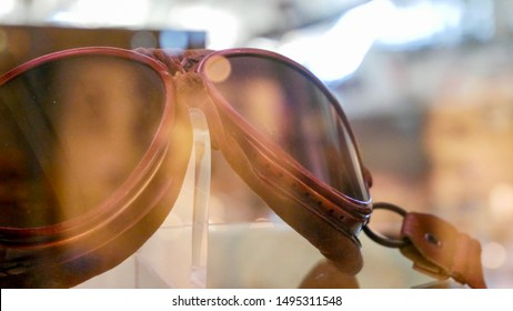 Antique airplane pilot goggles behind glass.