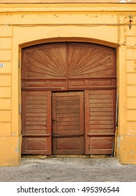 Antique arched house entrance with big carved wooden panels and paneled door