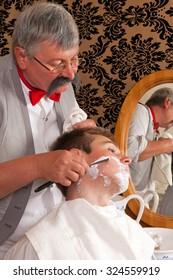 Antique barber shaving a customer with shaving cream