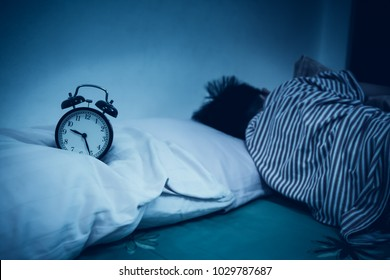 Antique black alarm clock in front of asian boy sleeping on bed in dark bedroom at home. Child relaxing napping at night. Image with selective focus.