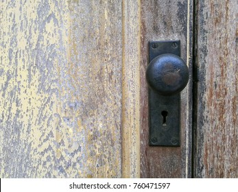 Antique black knob with key hole made from metal stuck on painted wooden door and left space