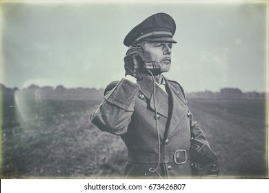 Antique black and white photo of 1940s military officer calling with field phone while standing on farmland.
