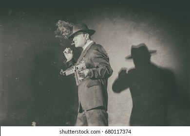 Antique black and white photo of 1940s film noir gangster with gun smoking cigarette.