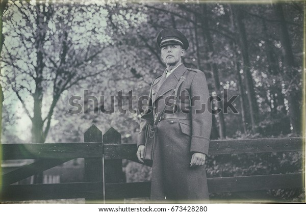 Antique black and white photo look of 1940s military officer standing at wooden fence in autumn forest.