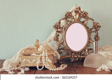 Antique blank victorian style frame, perfume bottle and white pearls on wooden table. template, ready to put photography