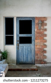 Antique blue wood doors and window with red brick wall and lamb.