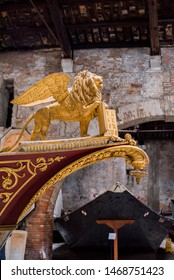 antique boats in a warehouse, italian boats, golden lion figurehead