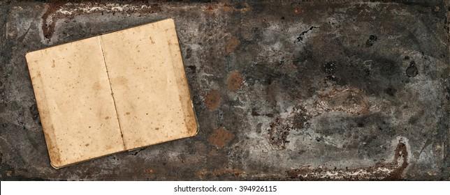Antique book on rustic metal table surface. Vintage style background