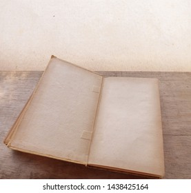Antique book open on rustic wooden table and aged background. Detachment for empty sheets, canvas for customization> Copy space